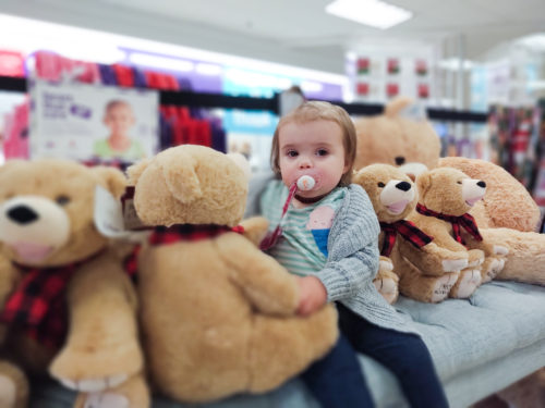 toddler looking at camera with teddy bear