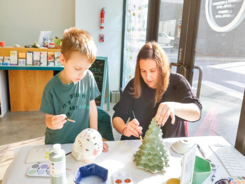 Mother and son painting pottery