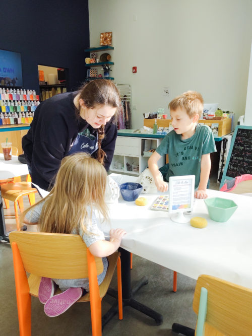 Kids painting pottery with adult